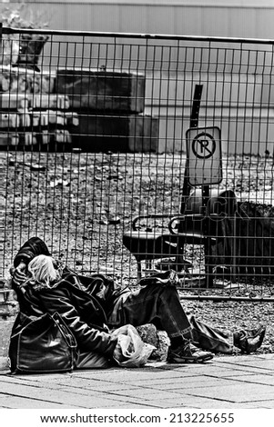 Old homeless men near construction site in black and white - stock photo