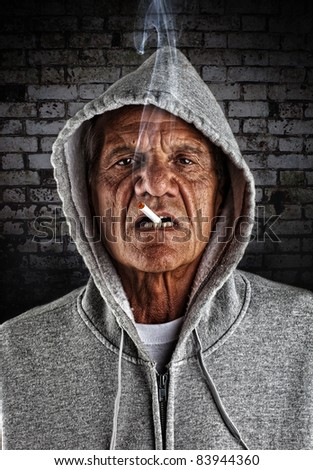 Old Hoodlum Smoking in an Alley - stock photo