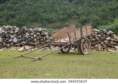 Old horse drawn wooden cart on grass field and stone wall behind - stock photo