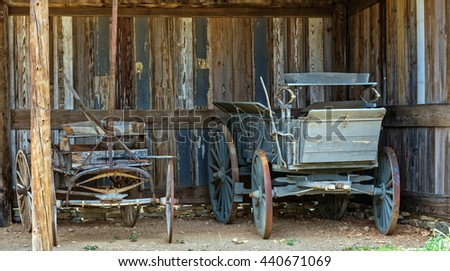 Old horse driven carriages in a barn - stock photo