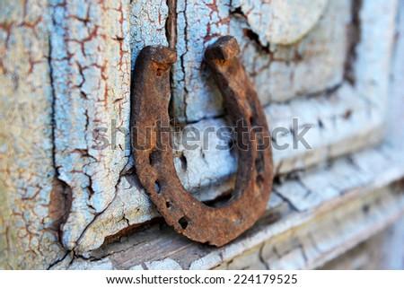 Old horse shoe on vintage wooden door, outdoors - stock photo