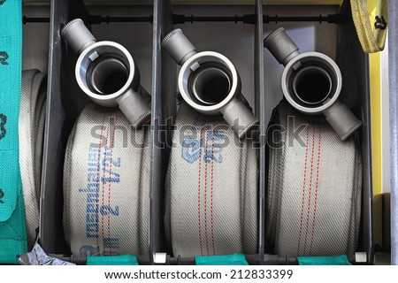 old hoses of firefighters in order inside the fire truck ready to put out the fire - stock photo