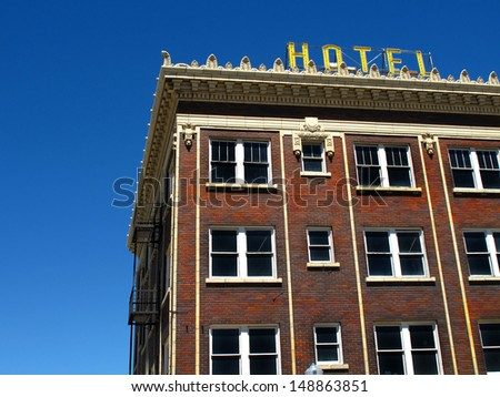 Old hotel with yellow sign and blue sky