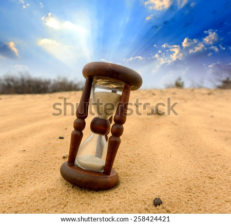 Old Hourglass in desert on sand - stock photo