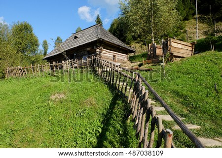 Old house and wooden staircase leading to it, in the wooded mountains on a sunny summer day