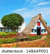 Old house-museum of the first settlers on the island of Madeira. Charming white cottage with a thatched roof and gable small garden with flowers - stock photo