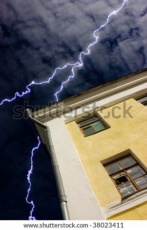old house on a background of clouds with lightning - stock photo