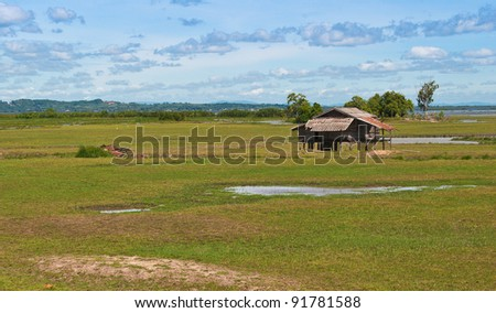 Old house on the meadow at thailand - stock photo