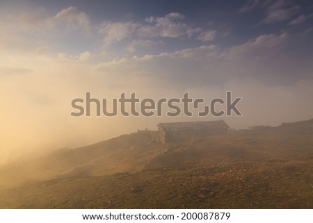 old house on top of a mountain in the clouds - stock photo