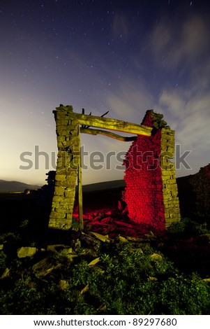 old house ruins in the countryside at night light painted - stock photo
