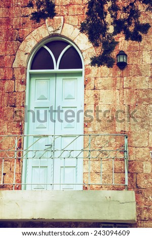 old house's wall from jerusalem stone with old blue balcony. filtered image - stock photo