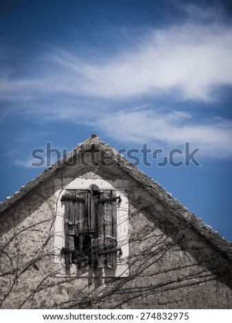 old house top with blue sky and clouds