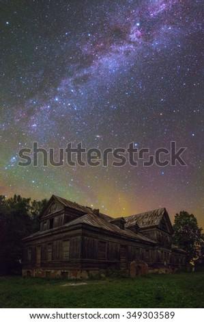 Old house under stars - stock photo