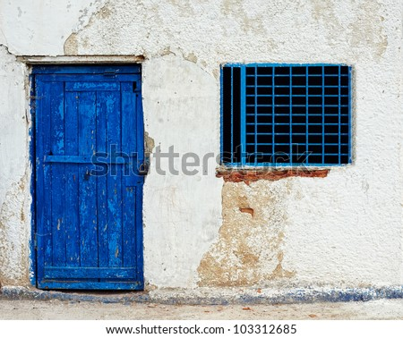 old house wall with blue door and window - stock photo