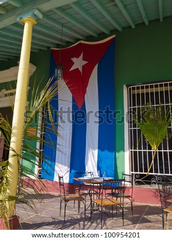 Old house with a cuban flag in the colonial town of Trinidad in Cuba, a famous touristic landmark on the caribbean island - stock photo