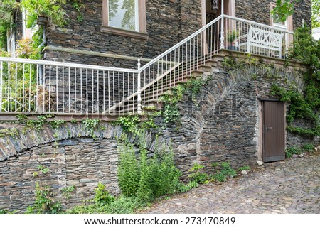 Old house with brick stone facade and stone stairs - stock photo