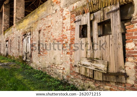 Old house with brick wall and window with wooden protection - stock photo