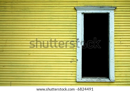 Old house with peeling paint and open door