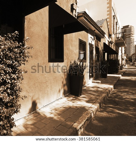Old Houses after Reconstruction in Tel Aviv on the Background of the Modern Building, Vintage Style Sepia  - stock photo