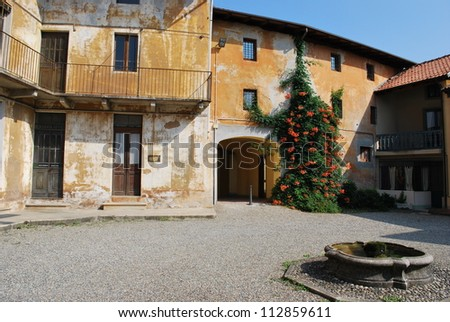 Old houses courtyard with fountain and flowers on the wall, Italy