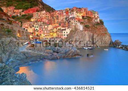 Old houses of Manarola village illuminated at dusk, Cinque Terre, Italy - stock photo