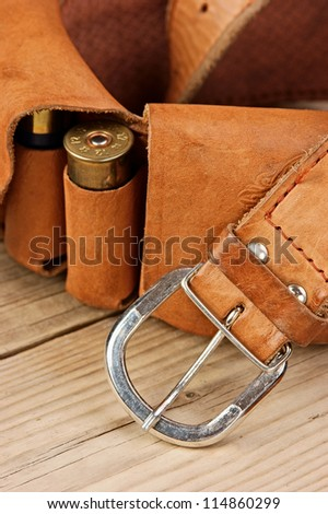 Old hunting cartridges and bandoleer on a wooden table - stock photo