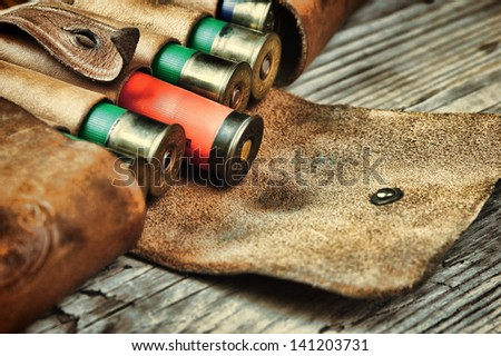 Old hunting cartridges and bandoleer on a wooden table