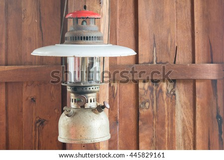 old hurricane lamp hanging on wooden  wall home - stock photo