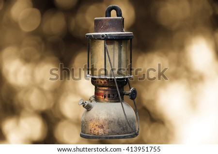 old hurricane lamp on sunny abstract background
