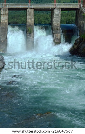 Old hydroelectric power plant at the Chemal river (Altai, Russia) for industrial electricity generation. The river, flow of water, bridge and dam are visible. Mountains and blue sky serve as backdrop. - stock photo