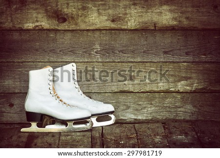 Old ice skates against rustic wooden background. Vintage filter effects. - stock photo