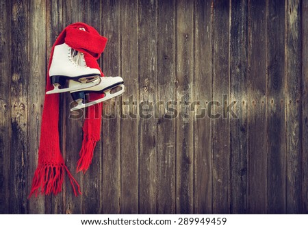 Old ice skates with a red scarf hanging on rustic wooden wall. Vintage filter effects. - stock photo