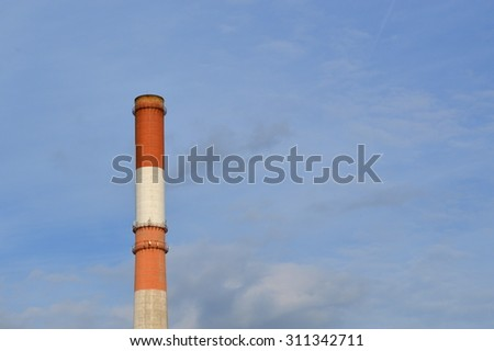 Old industrial chimney of energy generating plant in blue sky