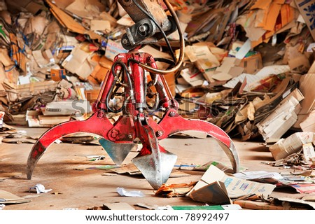 Old industrial claw in recycle paper junkyard - stock photo