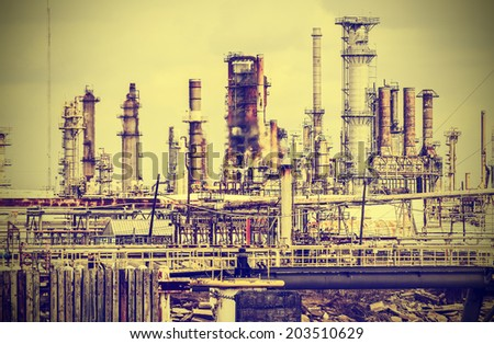 Old industrial plant with gray sky, vintage retro style. - stock photo