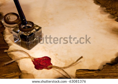 Old ink pot on a parchment scroll with wax seal - stock photo