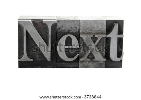 old, ink-stained metal letterpress type spells out the word 'Next' isolated on white