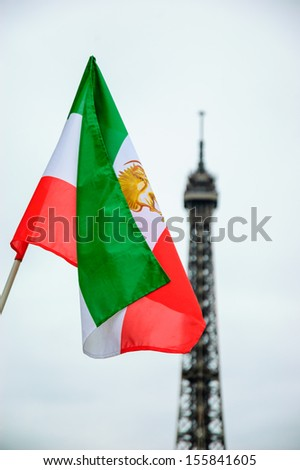 Old Iranian flag (Iran's flag under the former Shah regime) and Eiffel tower at background. Demonstration in Paris. - stock photo