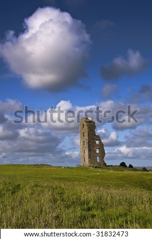 old irish castle ruins in green field with blue sky