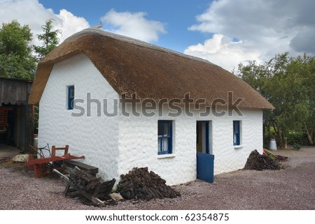 Old Irish thatched cottage with blue painted half door open to welcome visitors, while antique agricultural tools and stacks of turf lean against the wall.