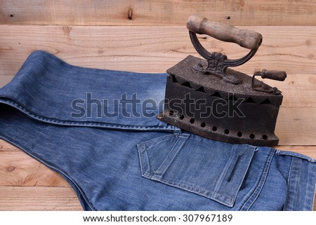 Old iron belt and jeans on a wooden floor.