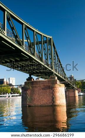 Old iron bridge in Frankfurt germany with brick pylons - stock photo