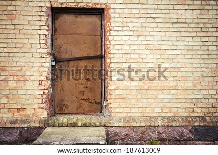 Old iron door in a yellow brick wall