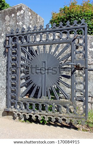 Old iron gate with a cross and granite wall at the entrance to a church at summer. - stock photo