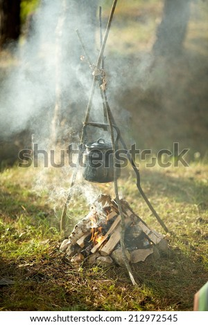 Old iron kettle on the fire, sparks fire - stock photo