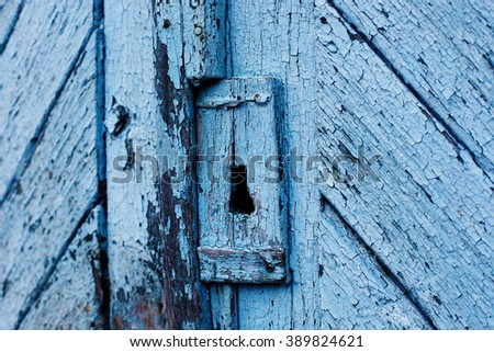 old iron lock with key hole in a damaged wooden door. Close up of keyhole on wooden door old style - stock photo
