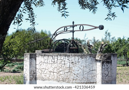 Old iron Noria traditionally used to remove water from the well for irrigation in agriculture - stock photo