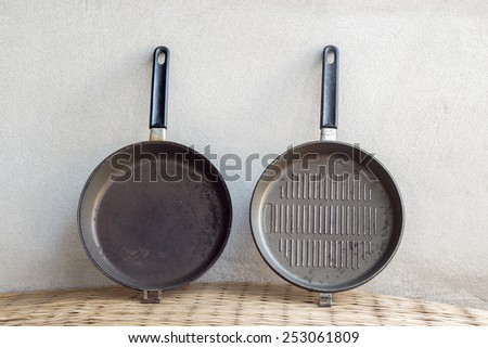 old iron pan still life on concrete wall background - stock photo