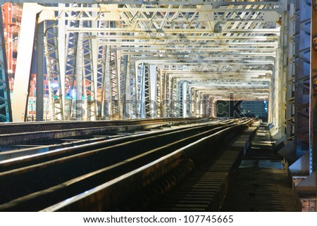 Old iron railway bridge for the passage of trains, at night. - stock photo