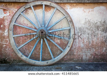 Old ironed, blue wagon or carriage wheel on old wall with peeling paint - stock photo